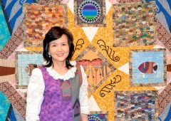 Sanae Nieda of Open House in front of one of her patchwork quilts.