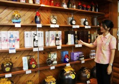A hostess explains the company line of different awamori at Zuisen showroom in Shuri.
