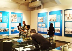 Visitors pore over exhibition items and photo panels at Himeyuri Peace Museum.