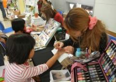 Children enjoy a body art session at Onna Issaigassai Festival.