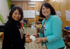 The AWWA President Melissa McDaniel presents a check to Chanpuru House Director Yumiko Yonaha to purchase a refrigerator for the facility that will allow Chanpuru House to conduct cooking classes and teach students about healthy eating.