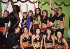 Global Village belly dancers pose for a photo while looking forward to Saturday's event.