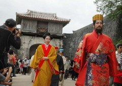 The Shuri Royal progression leaves the Shuri Castle while on-lookers snap photographs of the colorful spectacle.