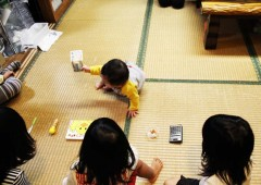 Rich shall I become! A baby picking up one of the items laid out on tatami on its first birthday is believed in Okinawa to predict its future.