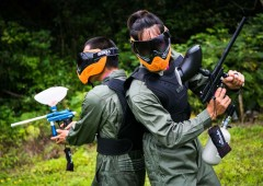Paintball game involves intense team work, crawling and hiding.