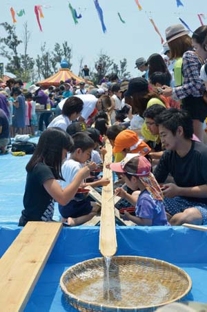 Visitors eat Nagashi Somen from a stream in a bamboo chute.
