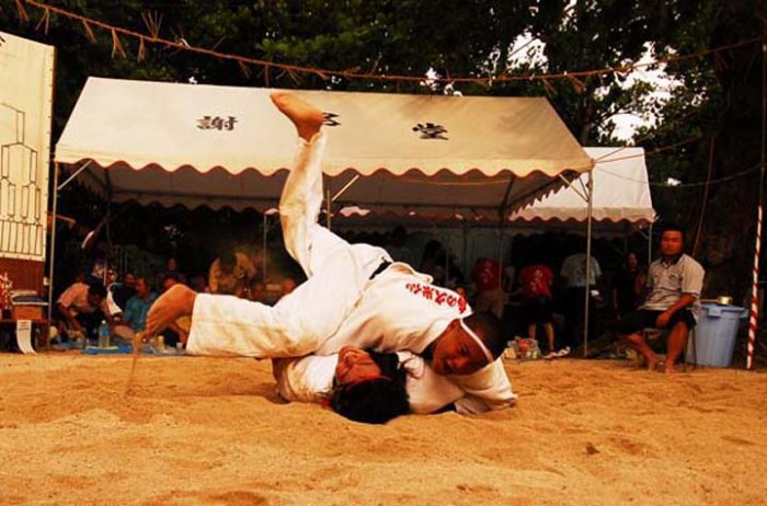 Okinawan sumo bouts take place on sand and with no ring or boundaries, and the aim is simply to topple the opponent on his back.