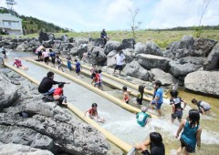 Children enjoy playing in the Taiho Dam overflow channel.