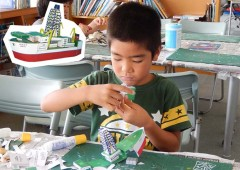 A student is putting together a paper model of a GODAC ocean exploration ship.