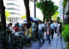 People line up t buy their daily bento lunch outside a Naha office building.