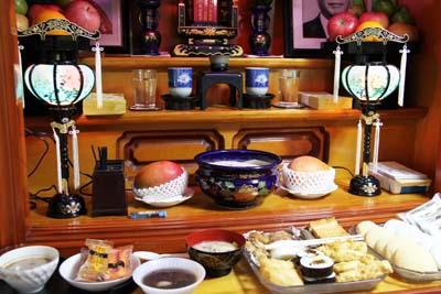 Special Obon foods and incense is set in front of a home altar.