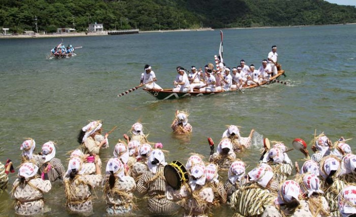 Women wade into the ocean to greet and encourage Haarii crews at the highlight of the Unjami Festival.