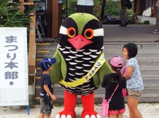 "Kunigami mascot ""Kui-chan"" greets children at the festival."