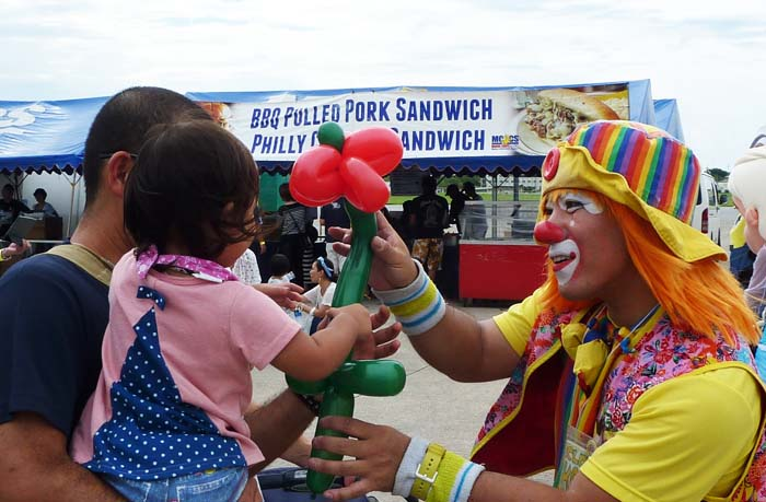 Clown Kotora entertains a young festival visitor. (MCCS photo)