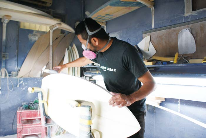 Mamoru Itokazu shapes a surfboard in his shop M's Surfshack.