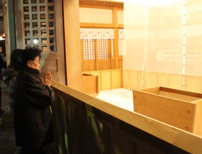 A woman prays at a shrine after throwing coins into the wooden saisen-bako offering box in front of her.