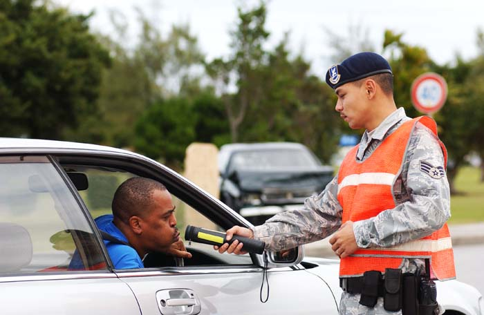 Senior Airman John Camacho, 18th Security Forces Squadron traffic safety unit, makes a traffic checkpoint to conduct a sobriety test using an alcohol detector at different areas on the base December 23, 2008. Kadena law enforcement officials and Okinawa police will exercise increased vigilance during the holidays to prevent drunk driving and keep the roads safe.  (U.S. Air Force photo/Tech. Sgt. Rey Ramon)