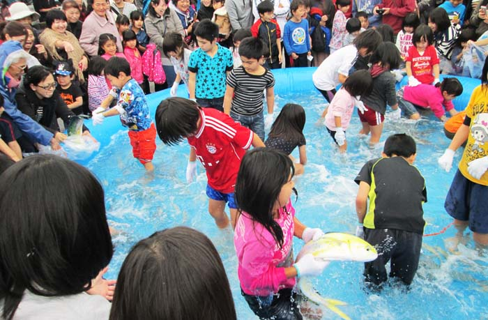 Children enjoy bare-hand fish catching contest.