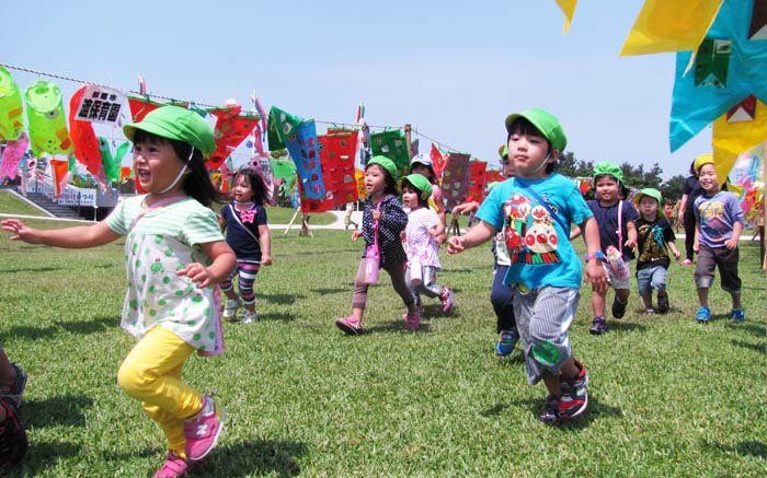 Children enjoy among koinobori streamers at Peace Memorial Park in Mabuni, Itoman.