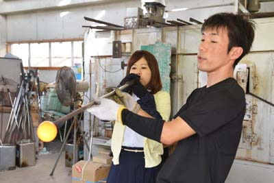 A visitor making a piece of Ryukyu glass.