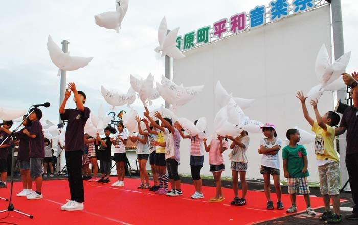 Students release dove-shaped balloons as a symbol of peace.