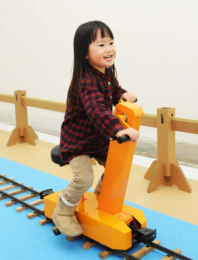 A child enjoys riding on a handcar along the playground tracks.