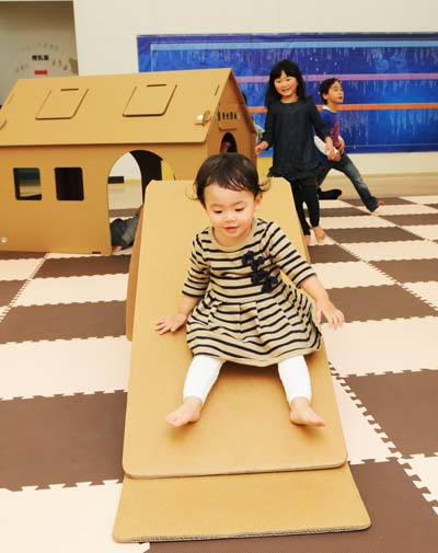 A slide and playhouse made of cardboard.