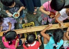 Children enjoy Nagashi Somen at an outdoor party.