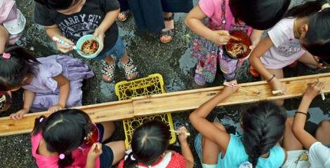 Children enjoy Nagashi Somen at an outdoor party.