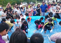 Elementary school students compete in grabbing live fish.