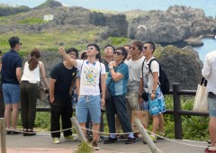 A Group of Chinese tourists taking selfies at a sightseeing spot is a common sight.